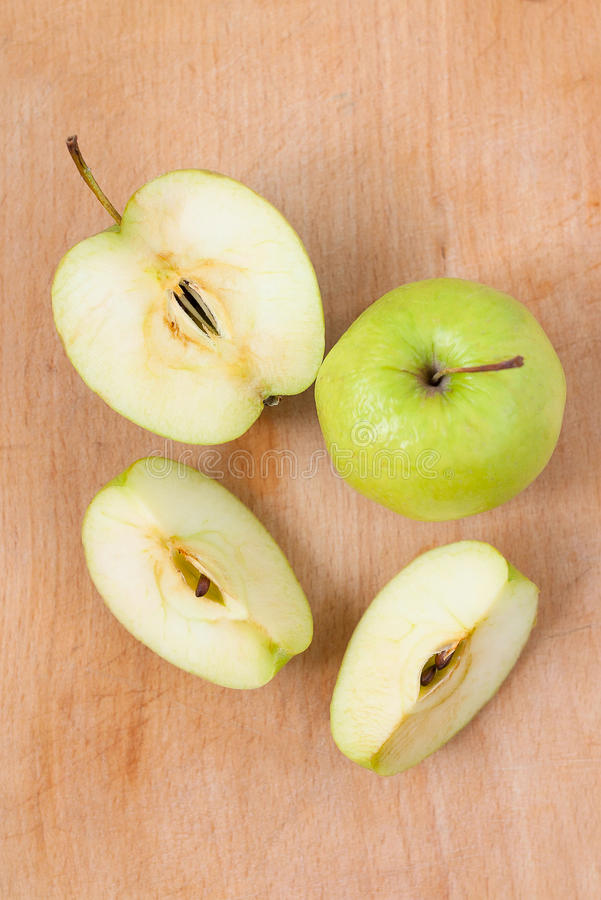 Fresh apples on a wooden Board. Green Apple cut into pieces. Fresh apples on a wooden Board. Green Apple cut into pieces is on a wooden texture royalty free stock photography
