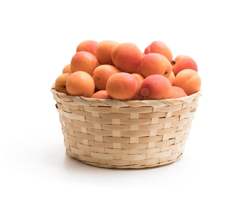 Fresh apricot in wicker basket isolated on white stock photography