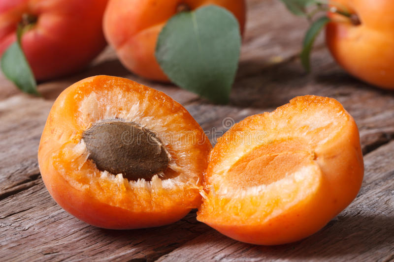 Fresh apricots halves closeup on wooden background. Horizontal royalty free stock images