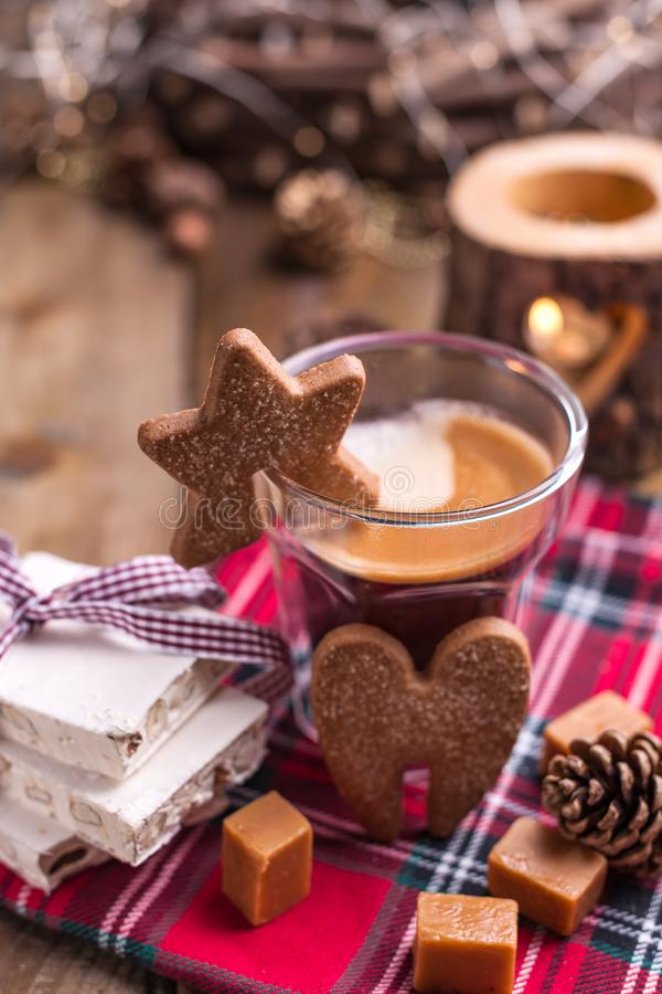 Fresh aromatic coffee and Italian Christmas sweets. Nougat with almonds, karemelnye sweets, ginger cookies and hot drink. Candles. And holiday decorations. Free royalty free stock image