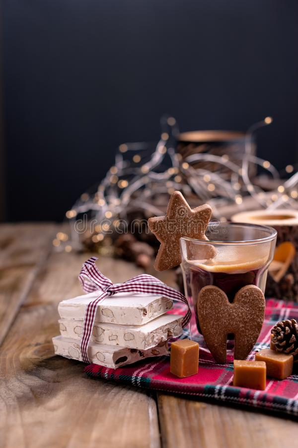Fresh aromatic coffee and Italian Christmas sweets. Nougat with almonds, karemelnye sweets, ginger cookies and hot drink. Candles. And holiday decorations. Free stock images