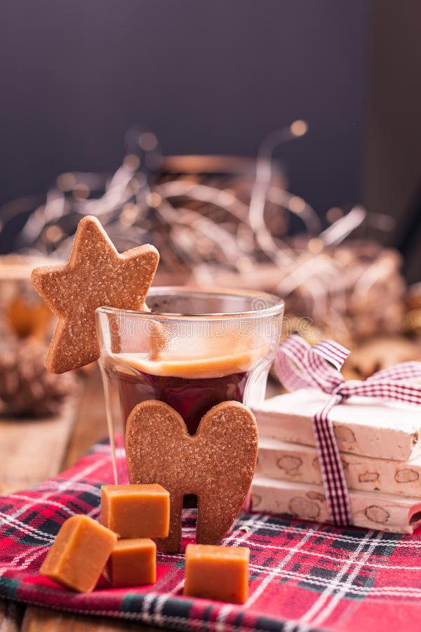 Fresh aromatic coffee and Italian Christmas sweets. Nougat with almonds, karemelnye sweets, ginger cookies and hot drink. Candles. And holiday decorations. Free royalty free stock images