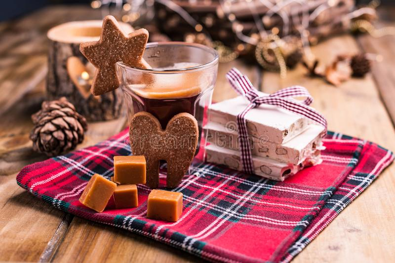 Fresh aromatic coffee and Italian Christmas sweets. Nougat with almonds, karemelnye sweets, ginger cookies and hot drink. Candles. And holiday decorations. Free stock photos