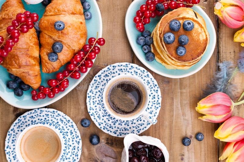 Fresh aromatic coffee in a vintage cup, pastry croissants and pancakes for breakfast with blueberries and currants, on a wooden stock photos