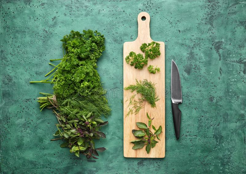 Fresh aromatic herbs with wooden board and knife on color table royalty free stock photo