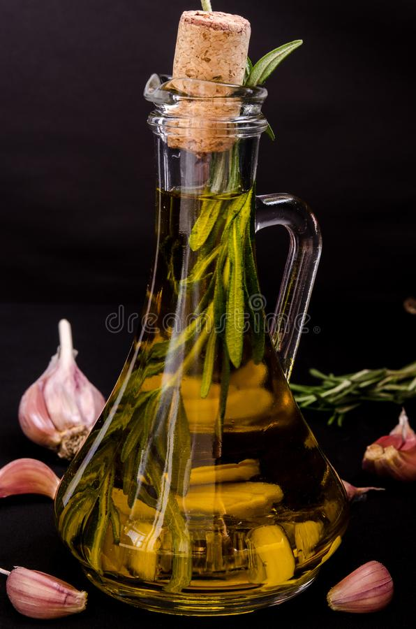 Fresh aromatic olive oil with a sprig of fresh rosemary and garlic cloves in a glass bottle on a black background.  stock image