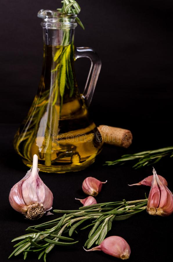 Fresh aromatic olive oil with a sprig of fresh rosemary and garlic cloves in a glass bottle on a black background.  royalty free stock image