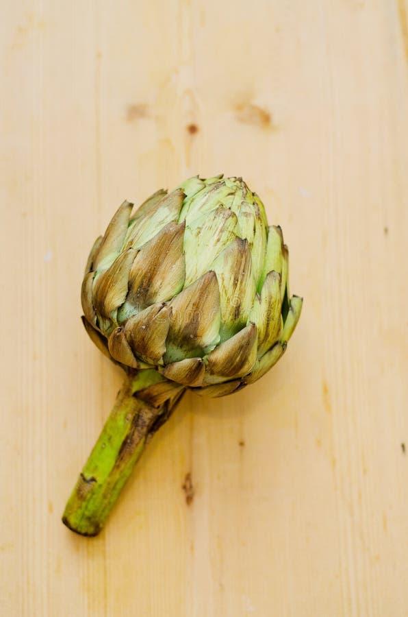 Fresh artichoke. Fresh first quality artichoke on wooden table stock photos