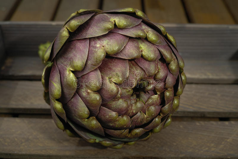 Fresh artichoke green-purple flower head, on wooden background. Fresh big Romanesco artichoke green-purple flower head, on wooden background royalty free stock images