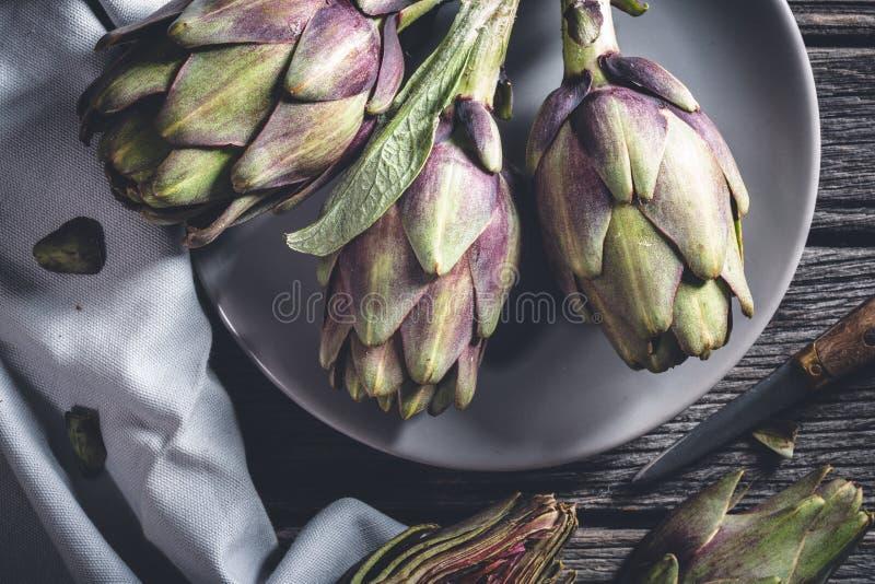 Fresh Artichoke. On wooden background stock photos
