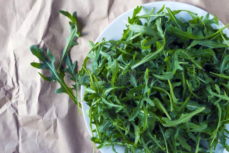 Fresh arugula Eruca, a cruciferous plant, and simply cabbage Brassicaceae on brown wrapping kraft paper. Rugula, Indau,  Walker, Caterpillar, Roshen Salad royalty free stock photo