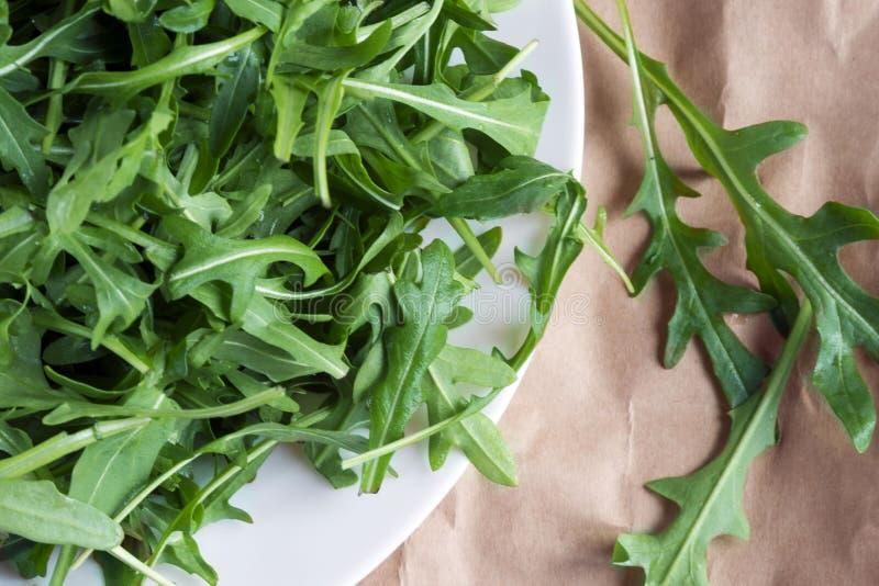 Fresh arugula Eruca, a cruciferous plant, and simply cabbage Brassicaceae on brown wrapping kraft paper. Rugula, Indau,  Walker, Caterpillar, Roshen Salad stock image