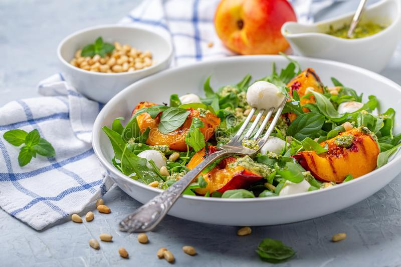 Fresh arugula salad with nectarines and pesto. Plate of fresh arugula salad with grilled nectarine, mozzarella and mint pesto on a gray textured background stock image