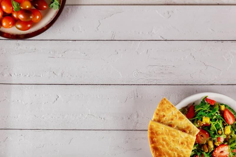 Fresh arugula salad with strawberry, mango, pistachios and pita bread royalty free stock image