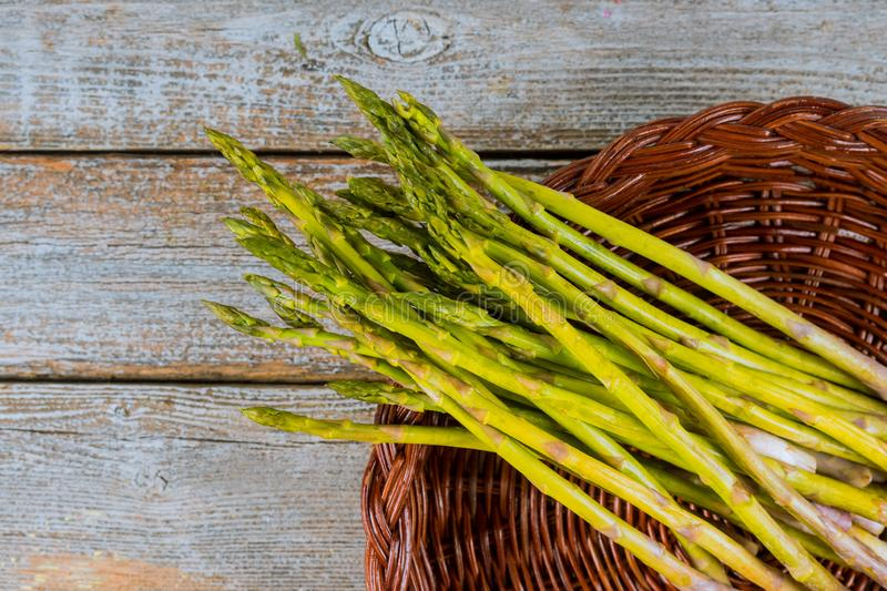 Fresh asparagus in brown basket on wood table stock photography