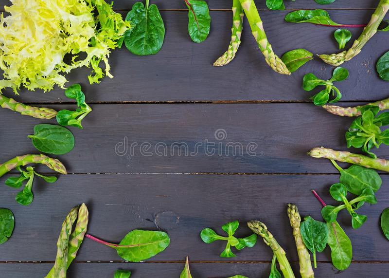 Fresh asparagus and green herbs on dark background. Top view royalty free stock image