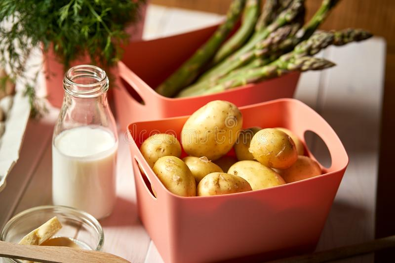 Fresh asparagus potatoes and chives on white  kitchen table royalty free stock image