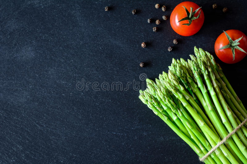 Fresh asparagus, tomatoes and spices royalty free stock photo