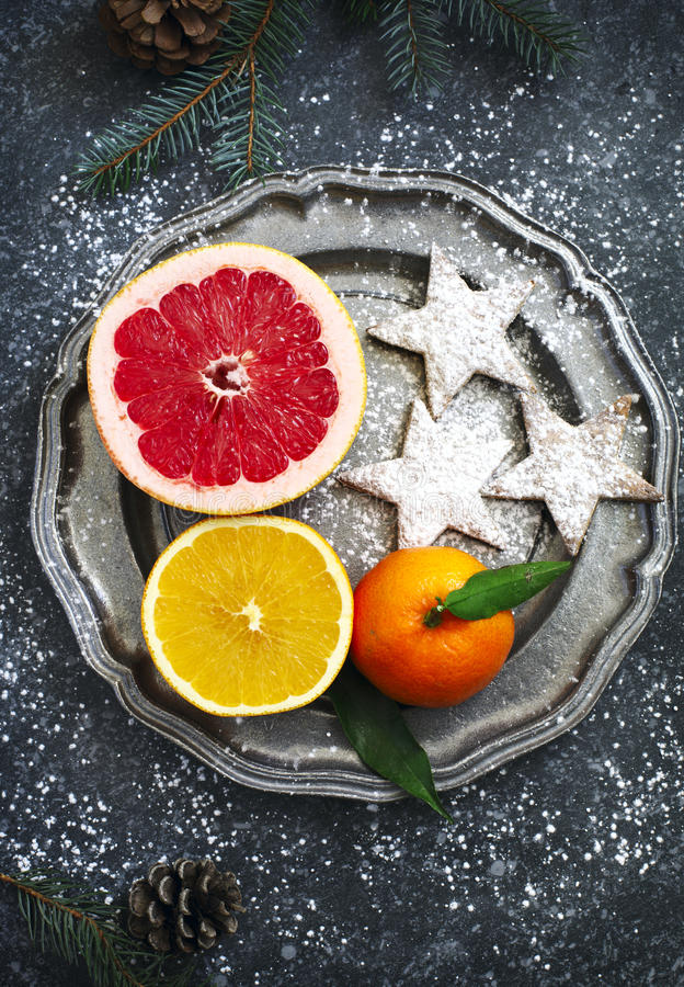 Fresh assorted citrus fruits and Christmas cookies on plate royalty free stock image