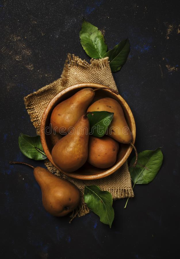 Fresh autumn brown pears in a bowl, top view stock photo