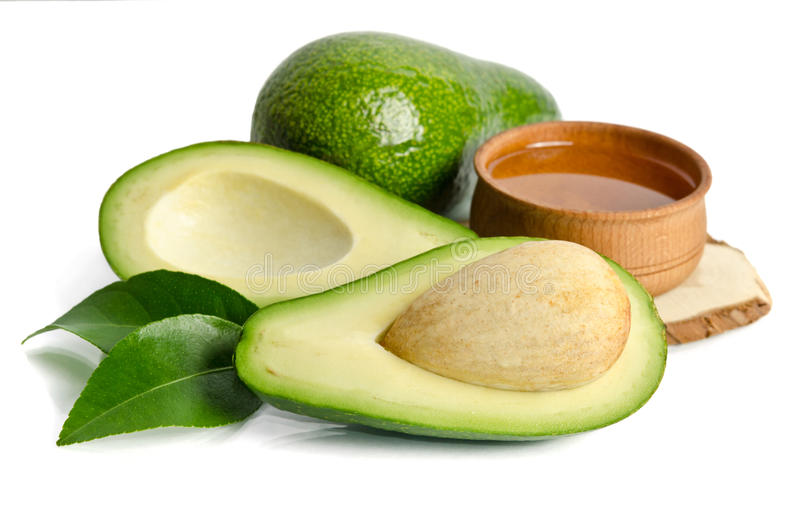 Fresh avocado with avocado oil in the wooden bowl stock photo