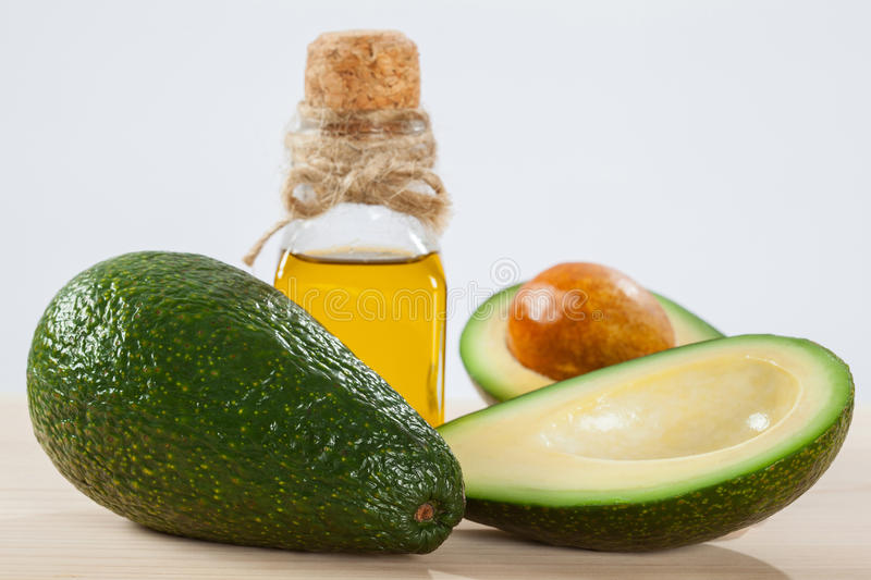 Fresh avocado and a bottle of oil stock image