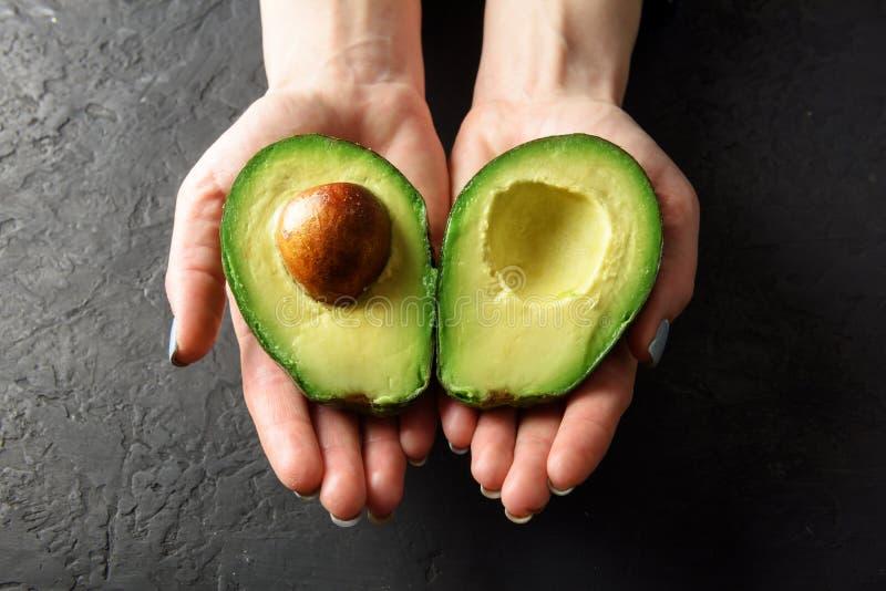Fresh avocado fruit in girl hands stock image