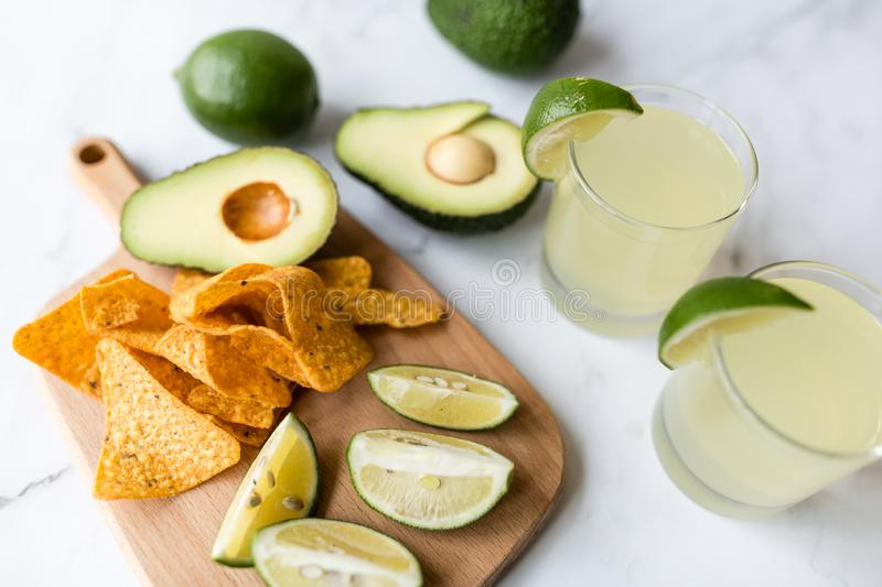 Fresh avocado, lime, drink and nacho chips lying on marble background. Recipe for Cinco de Mayo party stock photos