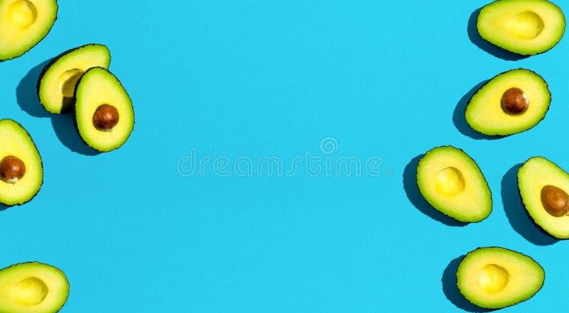 Fresh avocado pattern. On a blue background flat lay stock photos