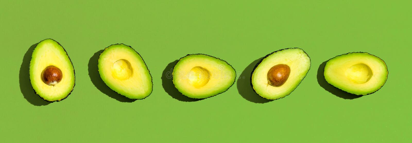 Fresh avocado pattern. On a green background flat lay royalty free stock photography