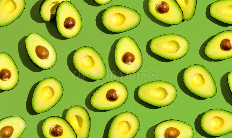 Fresh avocado pattern. On a green background flat lay stock images