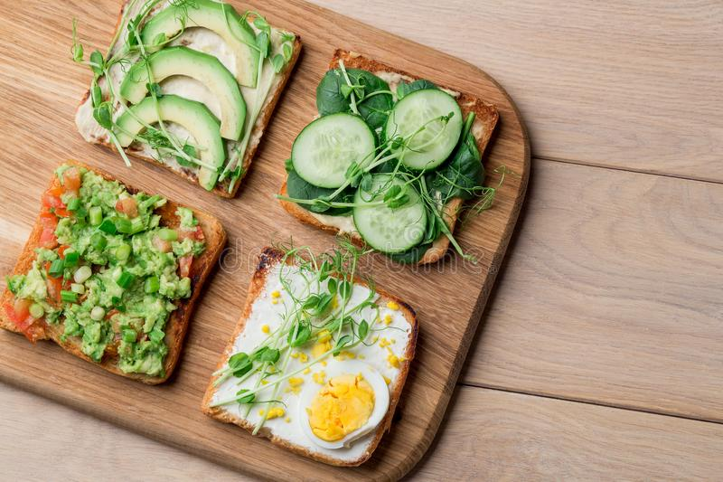Fresh avocado toasts with different toppings. Healthy vegetarian breakfast with rye whole grain sandwiches stock image