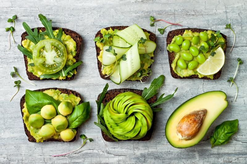 Fresh avocado toasts with different toppings. Healthy vegetarian breakfast with rye wholegrain sandwiches. stock photos