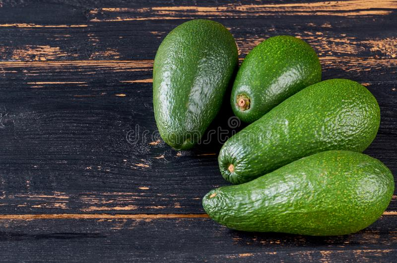 Fresh avocados on the dark wooden background with free copy space. Raw ingredients for veggie salad or diet dish. Side view stock photo