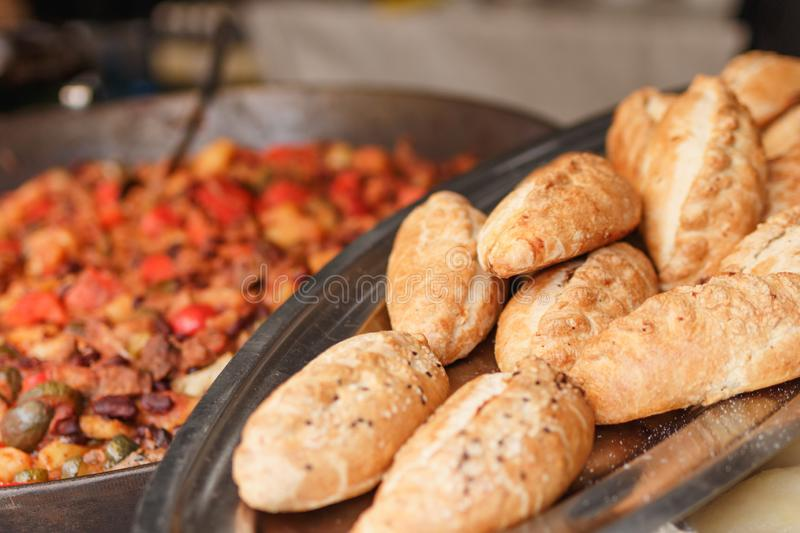 Fresh backed baguette bread with other meal background at the street food festival. Selective focus stock photography