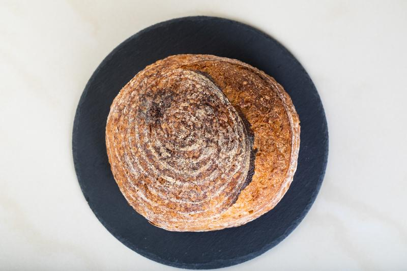 Fresh backed bread. Wholewheat bread on black round plate royalty free stock images