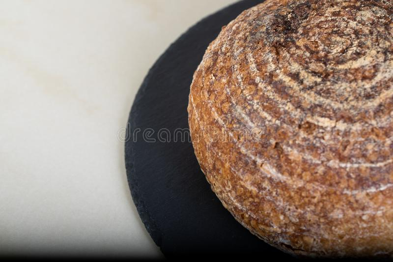 Fresh backed bread. Wholewheat bread on black round plate royalty free stock photography