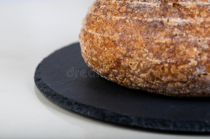 Fresh backed bread. Wholewheat bread on black round plate stock photography