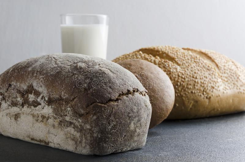 Fresh backed rye bread,bread with sesam seeds, rye bun, glass f milk on dark table in the kitchen.Closeup of different kinds of br stock photography