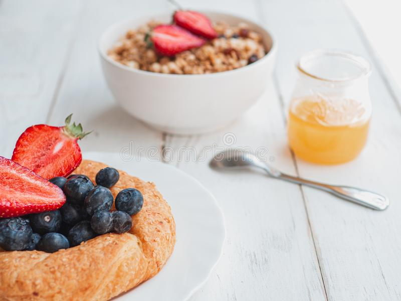 Fresh bagel with berries, oatmeal and honey on a white background. French summer breakfast stock images