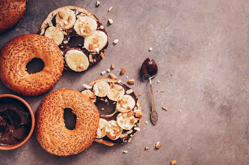 Fresh bagels with chocolate cream, banana and nuts on a dark rustic background. Delicious sweet breakfast. Top view, flat lay, stock photos