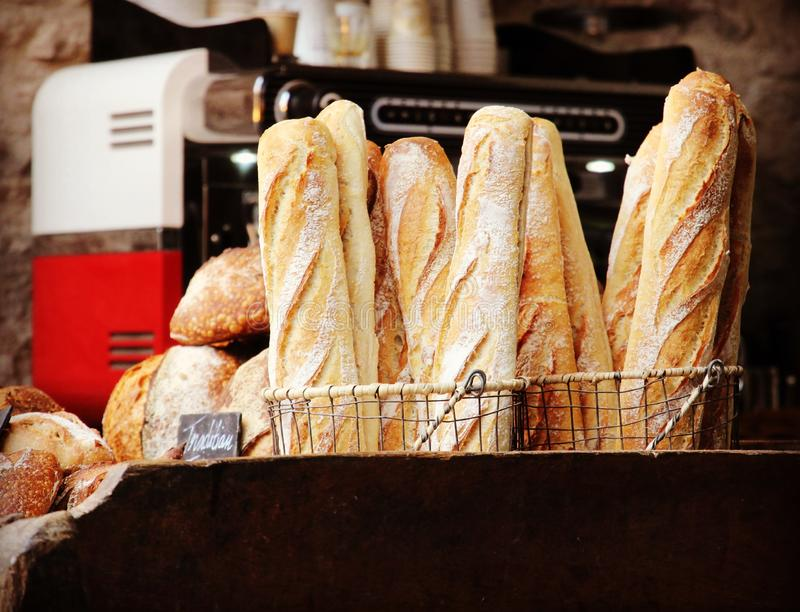Fresh Baguette Bread in Bakery. Fresh baguette and country bread with blurred barista coffee machine background in Edinburgh royalty free stock photography