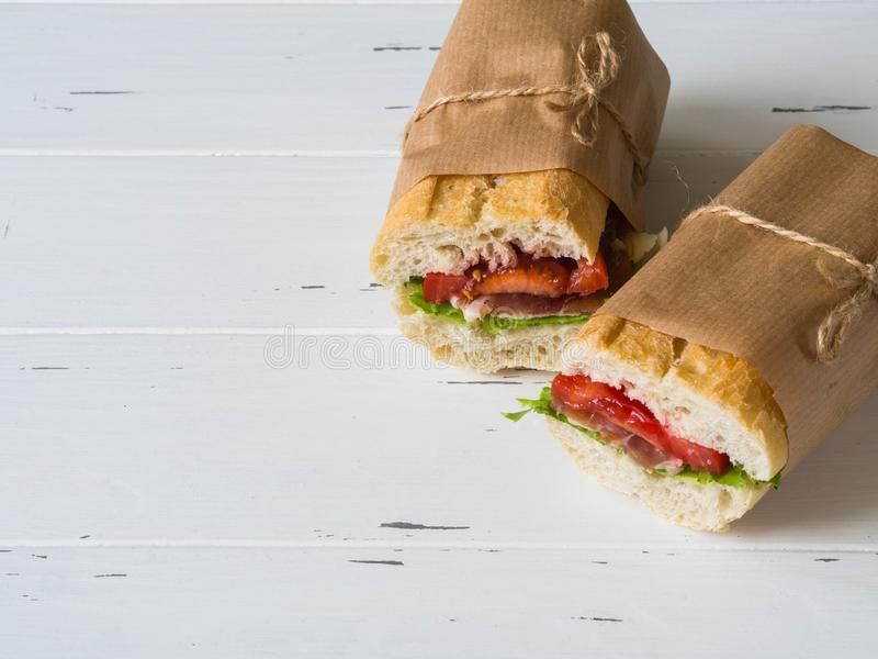 Fresh baguette sandwich with meat, sliced cheese, tomatoes and fresh lettuce in wrapping paper on white wood background. copy stock photography