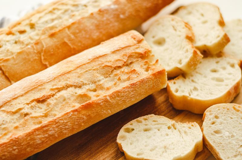 Fresh baguettes with crispy crust chopped on a cutting board on a white table. Tasty breakfast. royalty free stock photography
