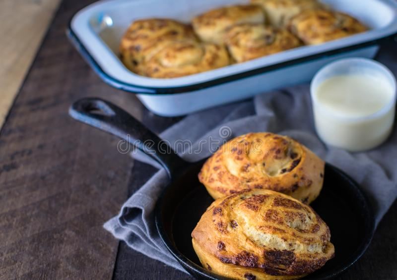 Fresh baked bread; frosting and cinnamon rolls on wooden table. Closeup cinnamon rolls in cast iron pan with cream cheese frosting; breakfast on wooden table stock images
