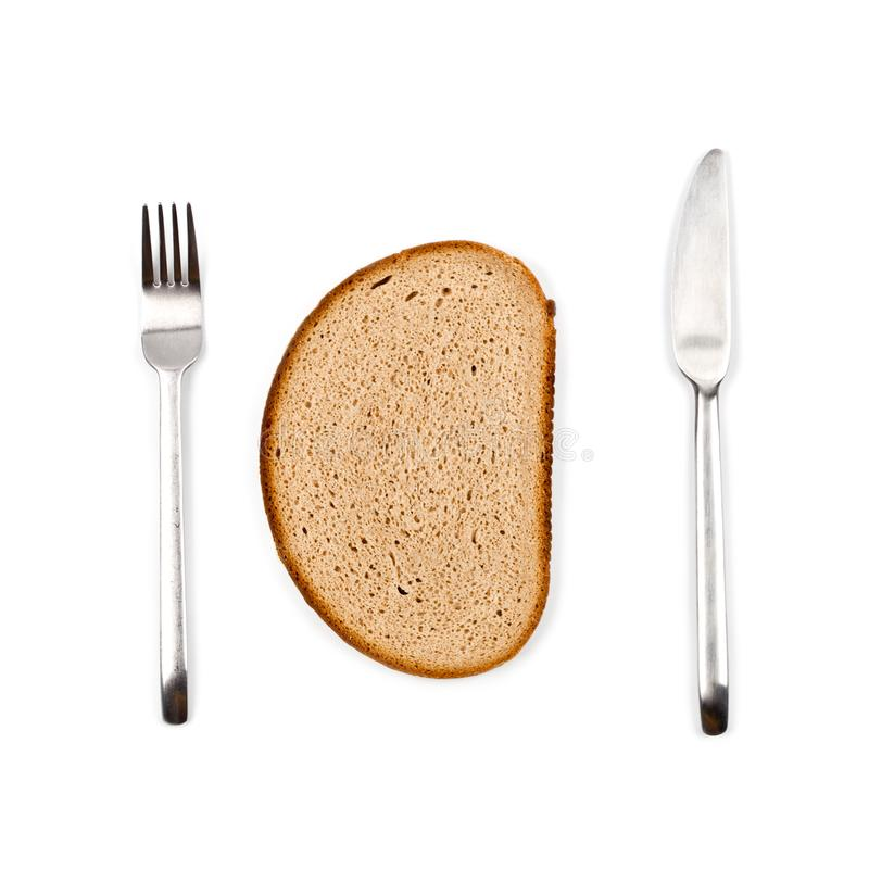 Fresh baked bread slice, fork and knife on white background. Top view image royalty free stock photo