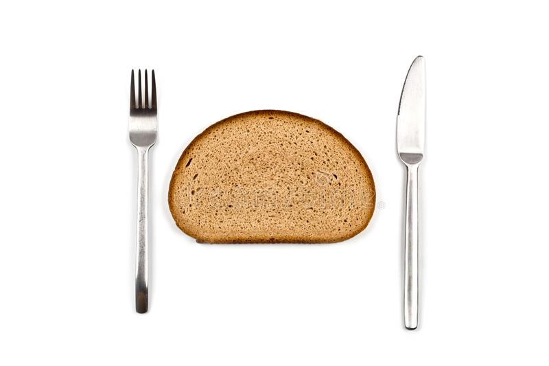 Fresh baked bread slice, fork and knife on white background. Top view image royalty free stock images