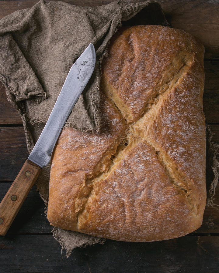 Fresh baked bread. Whole fresh baked artisan bread under sackcloth with vintage knife over old wooden background. Overhead view royalty free stock image