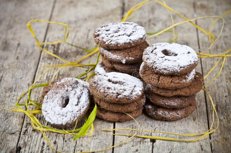 Fresh baked chocolate chip cookies with sugar powder stacks on wooden table. Background stock photos
