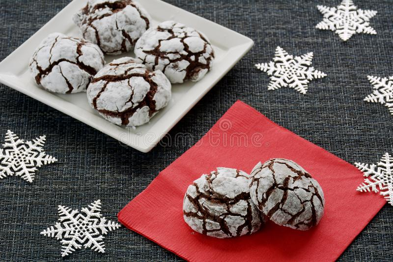 Chocolate crinkle cookies. Fresh baked chocolate crinkle cookies for a Christmas treat. Silver stars, red napkin, square white plate. Shot in natural light stock photo
